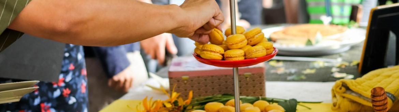 een hand neemt een lekkere gele macaron van een schaaltje